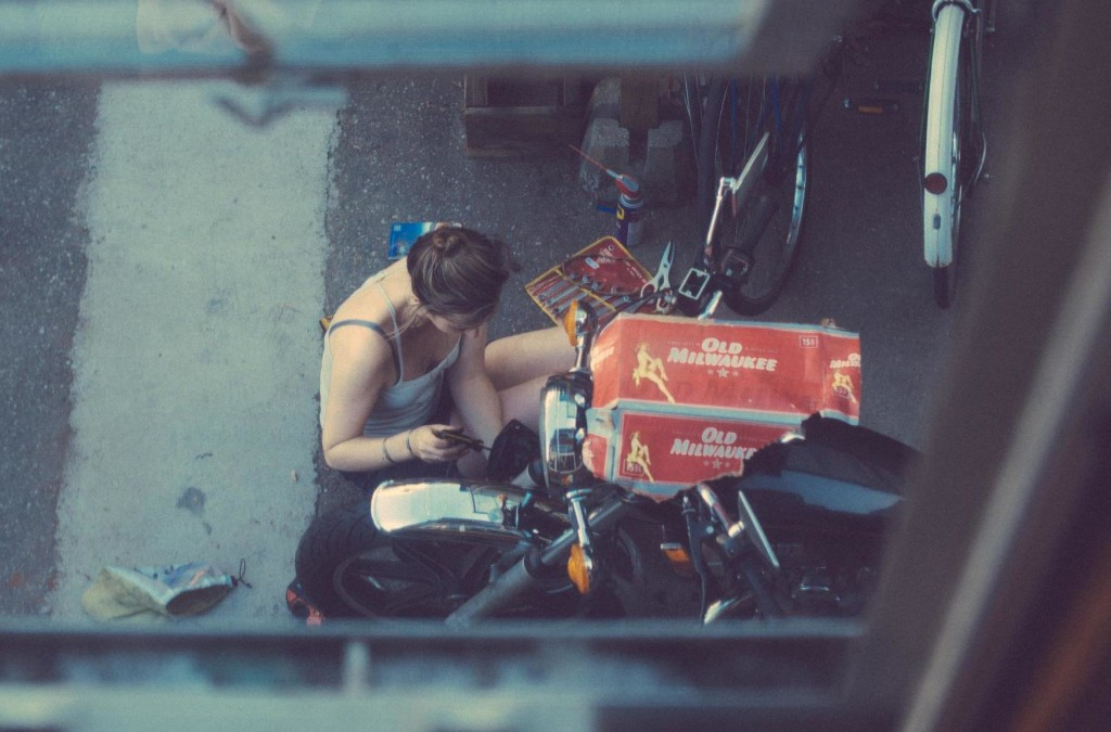 girl fixing her motorcycle