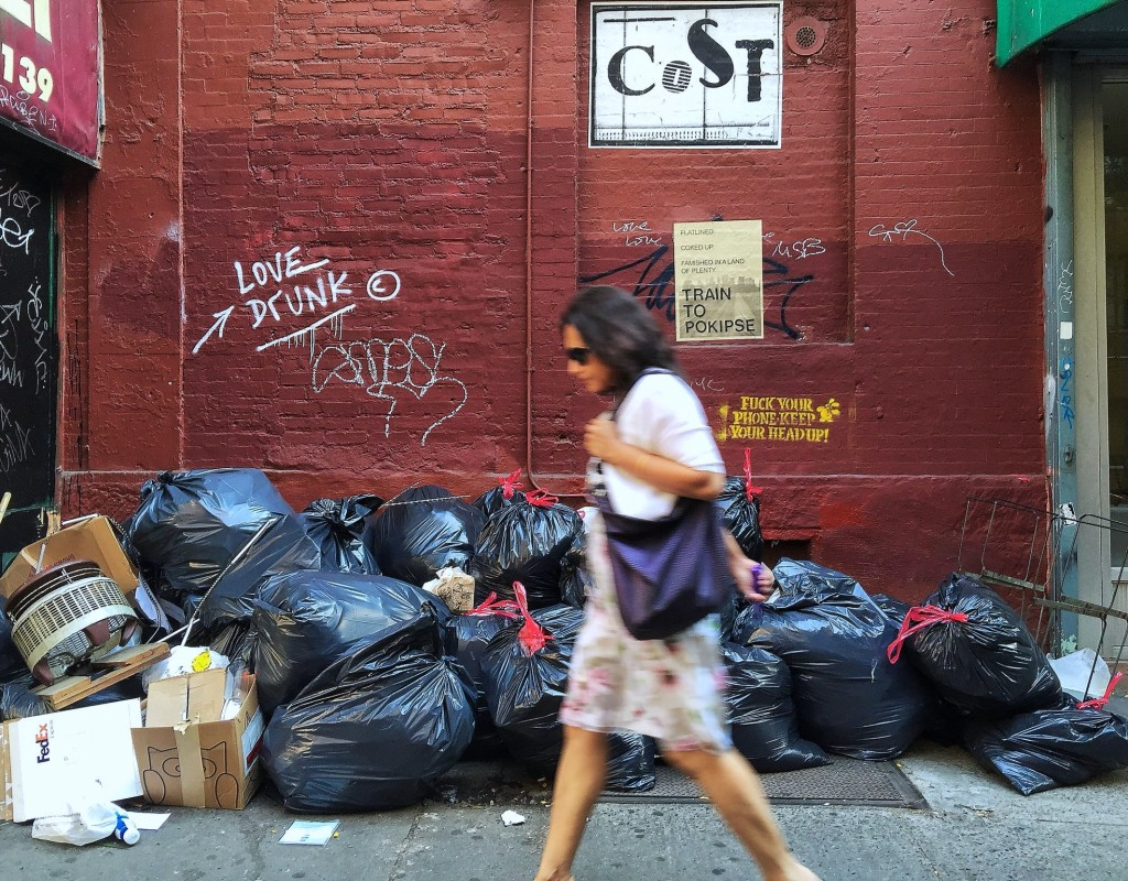 city woman walking past garbage in NYC