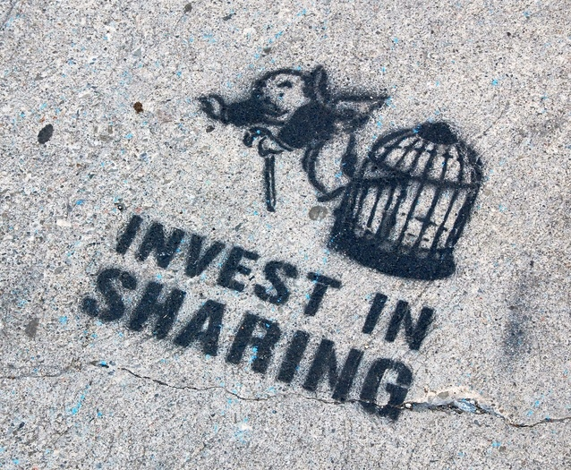"""Invest in sharing!"" A street art stencil featuring the ""get out of jail free"" card image from Monopoly board-game. Found painted on the sidewalk in New York City in 2007."